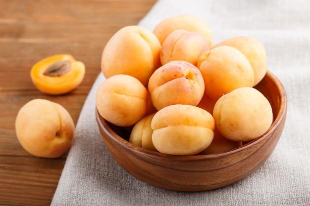 Свежие апельсиновые абрикосы в деревянной миске