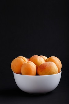 Fresh orange apricots in white bowl on black copyspace. side view.