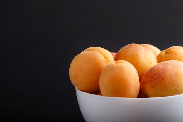 Fresh orange apricots in white bowl