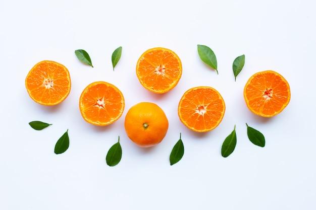 Fresh orange citrus fruit with green leaves on white.