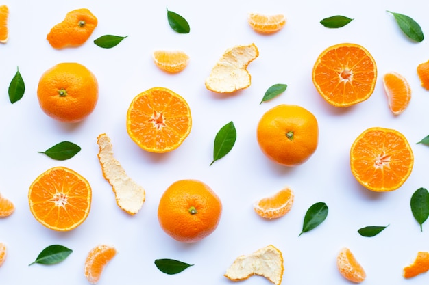 Fresh orange citrus fruit with peel and green leaves on white