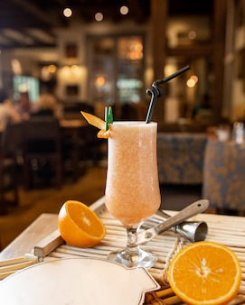 Fresh orange cocktail on the table with oranges