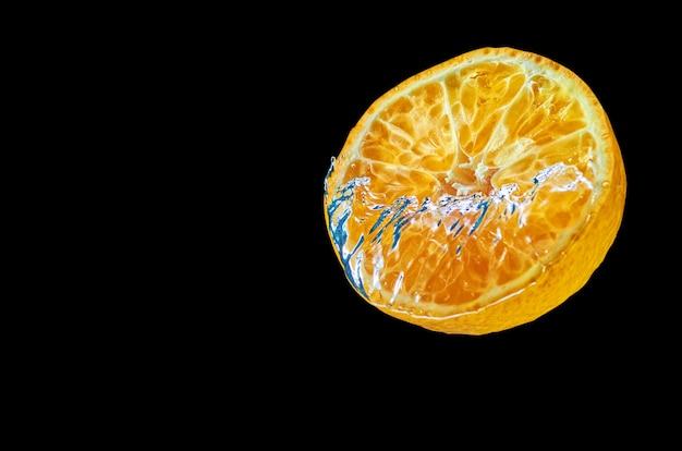 Свежий апельсин, падающий в воду с всплеск на черном фоне