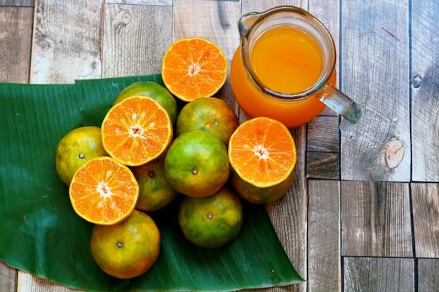 木製のテーブルに新鮮なオレンジ色の果物とオレンジジュース