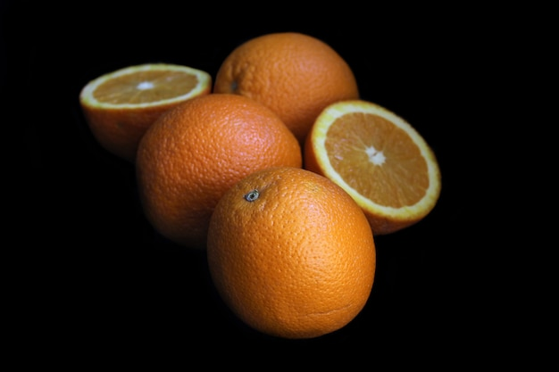 Fresh orange fruit, close up, on black background