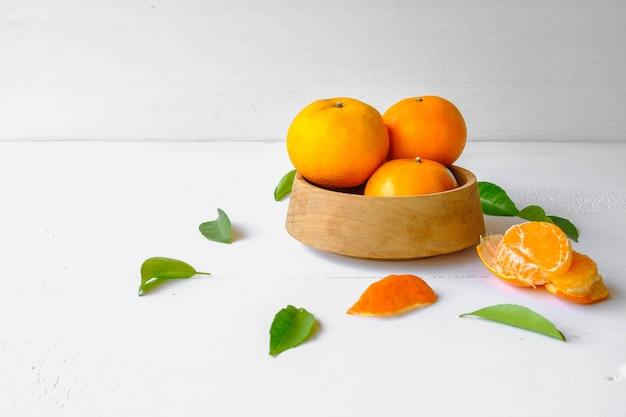 흰색 배경에 나무 그릇에 신선한 오렌지 과일