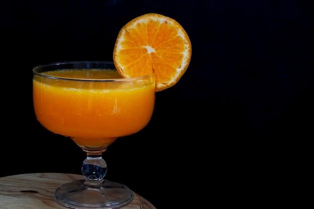 Fresh orange fruit makes orange juice in a glass on black background