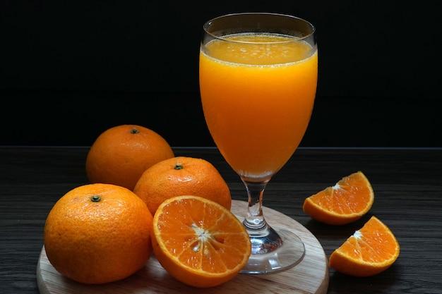 Fresh orange fruit makes orange juice in a glass