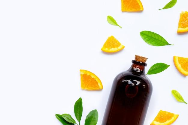 白い表面にエッセンシャルオイルのボトルと新鮮なオレンジ色の果物。
