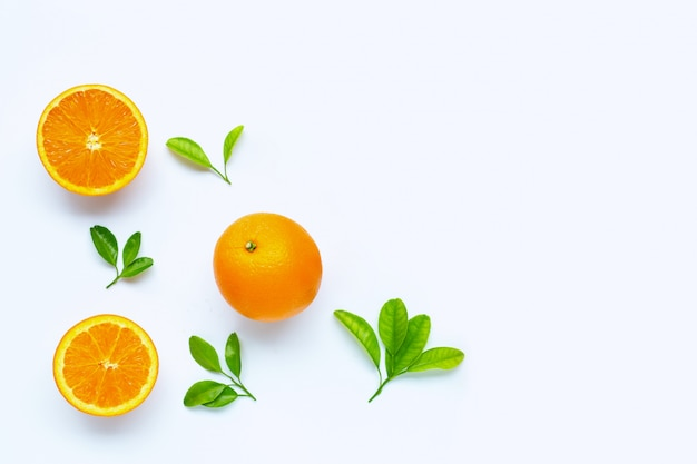 Fresh orange fruit with green leaves on white