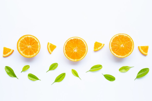 Fresh orange fruit with green leaves on white.