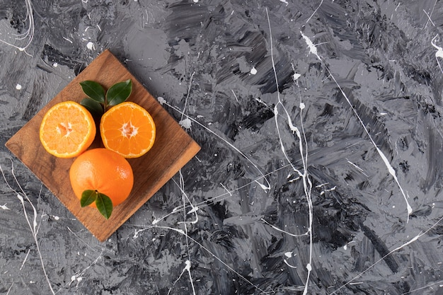 나무 접시에 신선한 오렌지 과일 대리석 표면에 배치