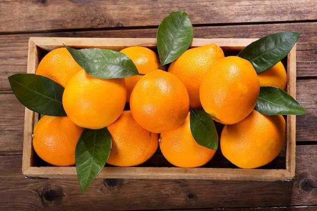 나무 테이블, 평면도에 상자에 잎을 가진 신선한 오렌지 과일