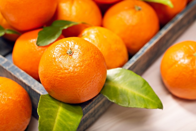 Fresh orange fruits with leaves on wooden table
