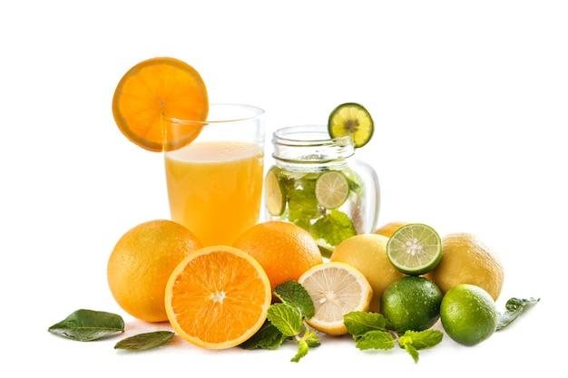 フレッシュオレンジジュースとクラシックなモヒートにオレンジ、ライム、ミントを白で分離