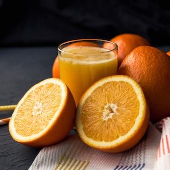 Свежий апельсиновый сок и свежие фруктовые апельсины на черной поверхности