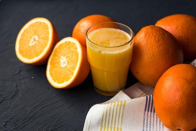 Свежий апельсиновый сок и свежие фруктовые апельсины на черном столе