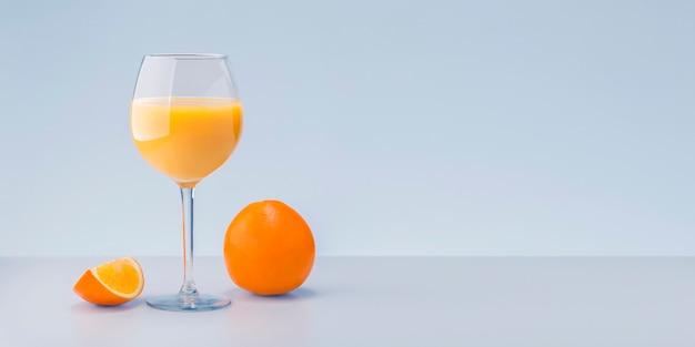 Свежий апельсиновый сок и фрукты на сером фоне с местом для текста.