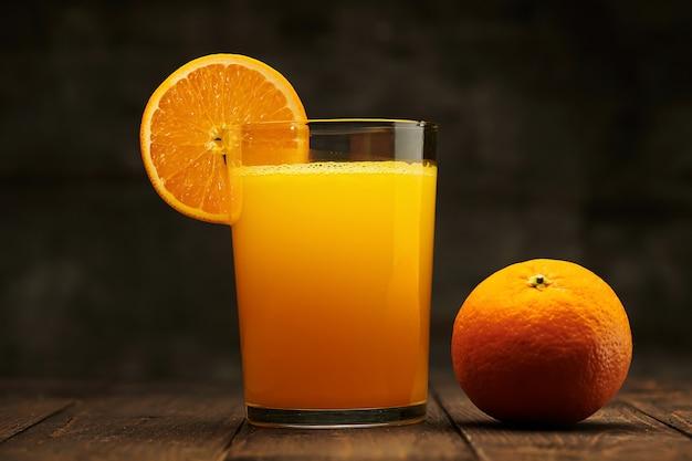 新鮮なオレンジジュースと果物を丸ごと木製のテーブルでスライスします-自然で健康的な食べ物と飲み物。フルーツのスライスとカクテル1杯