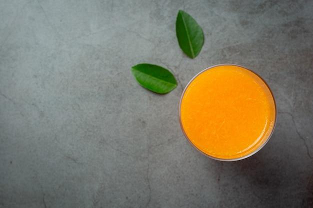 Fresh orange juice in the glass on dark background