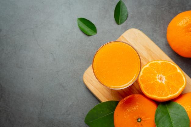 Succo d'arancia fresco nel bicchiere su sfondo scuro