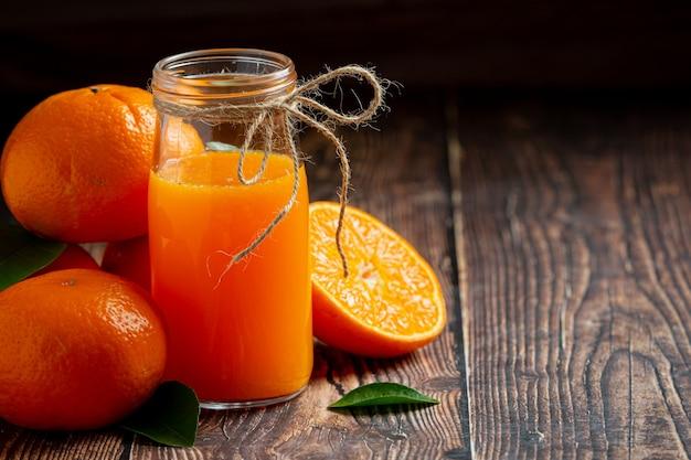 Succo d'arancia fresco nel bicchiere su fondo di legno scuro