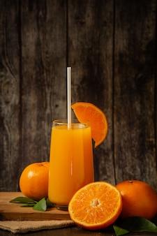 Succo d'arancia fresco in un bicchiere e arancia fresca
