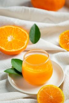 Succo d'arancia fresco nel bicchiere su fondo di marmo