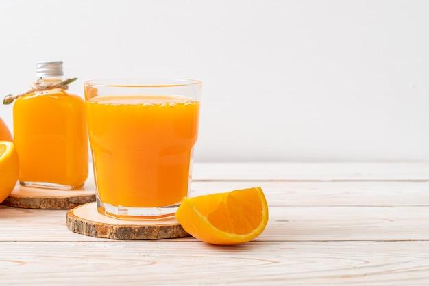 木の背景に新鮮なオレンジジュースのガラス