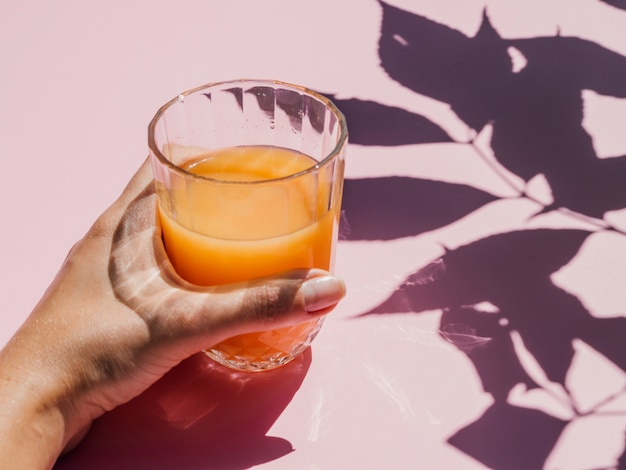 Fresh orange juice in glass and shadows