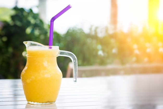 Fresh orange juice in glass in shape of a jug with a purple straw smoothie on white wooden table