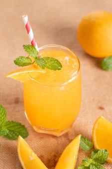 Succo d'arancia fresco in vetro con menta, frutta fresca. messa a fuoco selettiva.
