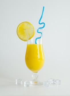 레몬 조각과 파란색 짚으로 장식된 유리에 신선한 오렌지 주스. 흰색 바탕에 여름 칵테일입니다. 화려한 디자인.