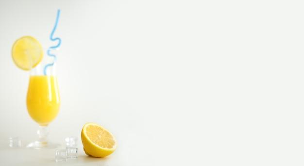 레몬 조각과 파란색 짚으로 장식된 유리에 신선한 오렌지 주스. 흰색 바탕에 여름 칵테일입니다. 다채로운 템플릿입니다. 텍스트를 위한 여유 공간, 복사 공간.