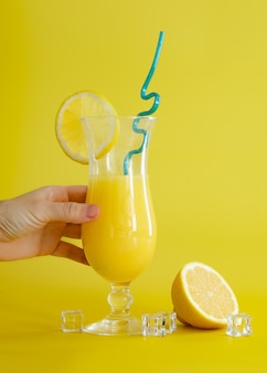 레몬 조각과 파란색 짚으로 장식된 유리에 신선한 오렌지 주스. 노란색 배경에 여름 칵테일입니다. 화려한 디자인.