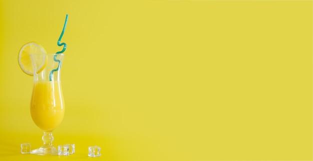 레몬 조각과 파란색 짚으로 장식된 유리에 신선한 오렌지 주스. 노란색 배경에 여름 칵테일입니다. 다채로운 템플릿입니다. 텍스트를 위한 여유 공간, 복사 공간.