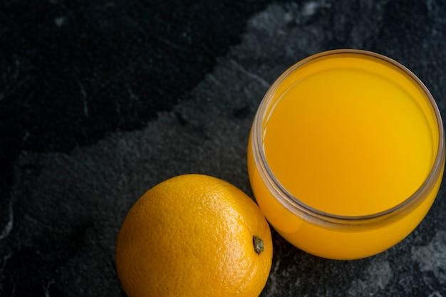 Свежий апельсиновый сок в стакане со свежими апельсиновыми цитрусовыми на темной поверхности
