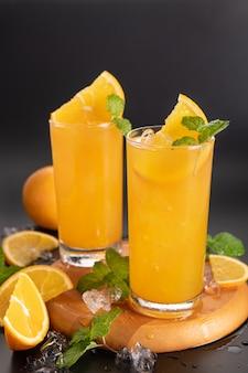 ガラスのフレッシュ オレンジ ジュース、ミント、フレッシュ フルーツ。セレクティブ フォーカス。