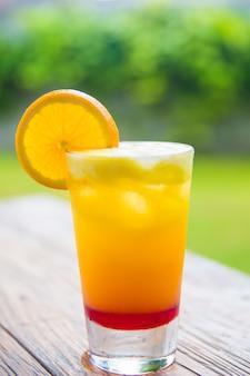 自然の背景を持つ木製の机の上のガラスの瓶に新鮮なオレンジジュース。休暇の概念。