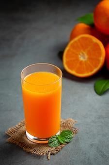 어두운 배경에 유리에 신선한 오렌지 주스