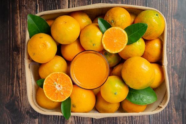 어두운 나무 배경에 유리에 신선한 오렌지 주스