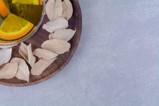 大理石のテーブルの上のガラスの新鮮なオレンジジュース。