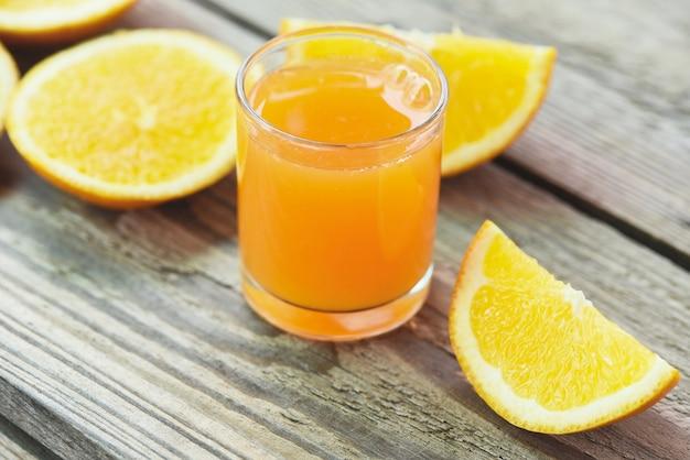 Свежий апельсиновый сок в стакане с апельсиновыми фруктами на деревянных здоровых фруктах и дольке апельсина