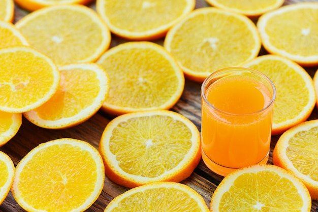 Свежий апельсиновый сок в стакане с апельсиновыми фруктами на деревянных здоровых фруктах