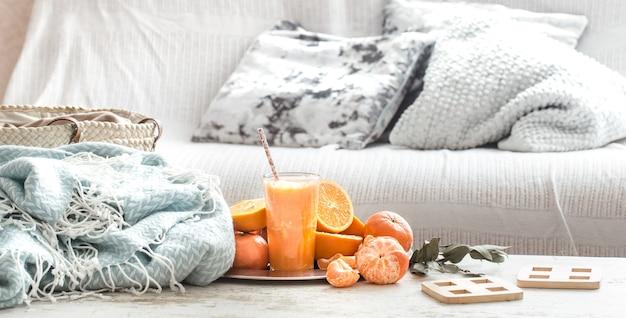 家の内部にある新鮮なオレンジジュース、ターコイズブルーの毛布とフルーツのバスケット