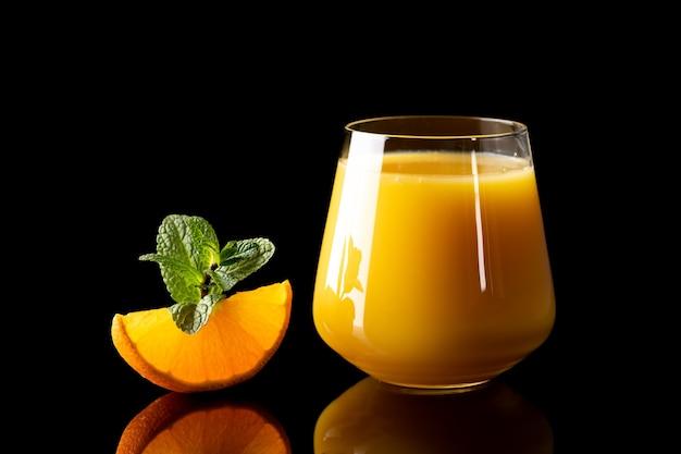 Свежий апельсиновый сок в стеклянный кубок на черном фоне