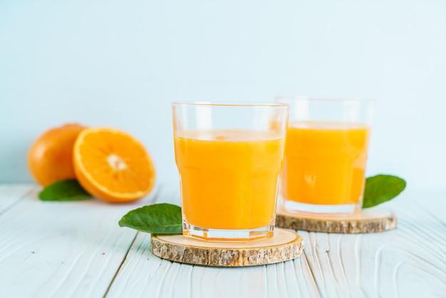 Свежевыжатый апельсиновый сок на фоне дерева