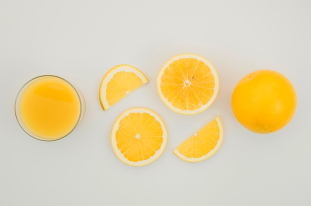 Fresh orange juice and slices on table