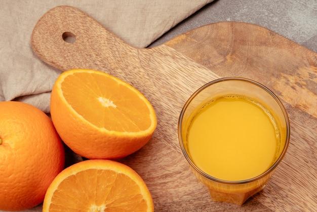 木の板とリネンのキッチンタオルに半分のオレンジが入ったフレッシュオレンジジュース。