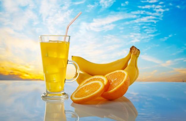 유리에 얼음과 신선한 오렌지 주스입니다. 오렌지와 일출 배경에 바나나